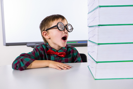 stacked books: Surprised boy by stacked books on table in classroom