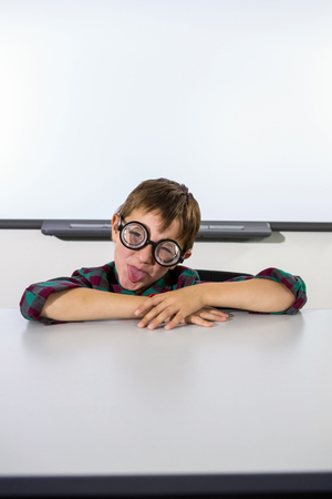 making a face: Playful boy making a face against whiteboard in classroom Stock Photo