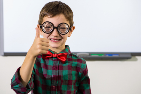 thumbs up sign: Portrait of smiling boy gesturing thumbs up sign in classroom