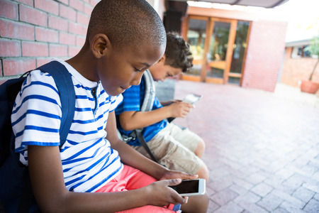 schoolboys: Schoolboys using mobile phones while sitting at corridor in school
