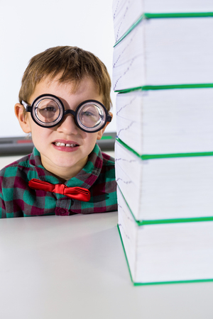 stacked books: Portrait of boy by stacked books on table in classroom Stock Photo