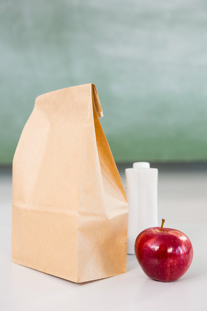 apple paper bag: Apple with drink bottle and paper bag on table in classroom Stock Photo