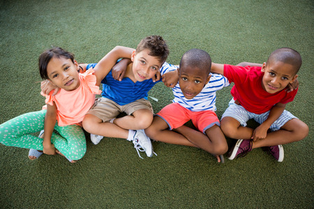 trato amable: High angle portrait of happy children sitting on grass at park Foto de archivo