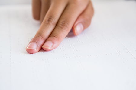 capable of learning: Cropped image of child hand reading braille book in classroom Stock Photo