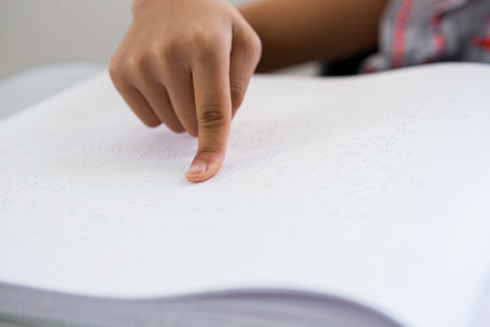 capable of learning: Cropped image of child reading braille book in classroom