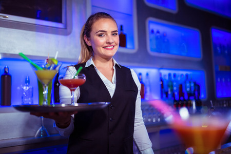 bartending: Portrait of beautiful bartender holding serving tray with cocktails in nightclub