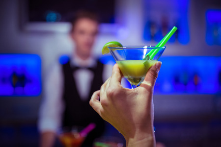 bartending: Cropped hand of customer holding cocktail glass against bartender at nightclub