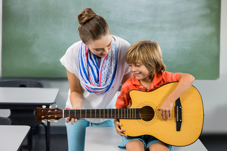boy playing guitar: Teacher assisting boy to play guitar in classroom