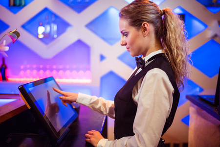 Side view of young barmaid using modern cash register at bar counter