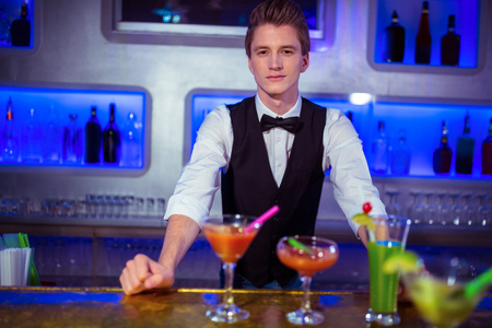 bartending: Portrait of confident male bartender standing at nightclub