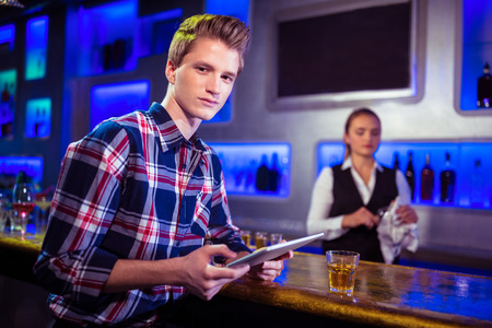 causal clothing: Portrait of young man using digital tablet with bartender working at nightclub