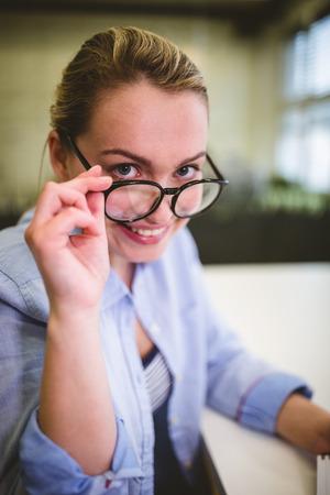 creative artist: Portrait of smiling businesswoman adjusting eyeglasses in creative office Stock Photo
