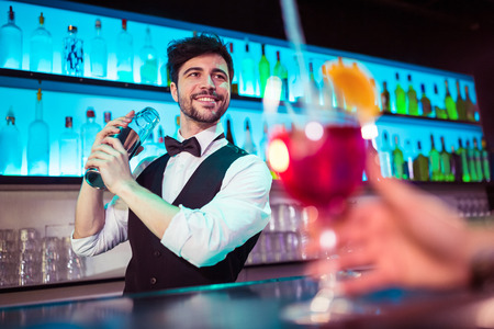bar counter: Barkeeper preparing cocktail for customer at bar counter Stock Photo