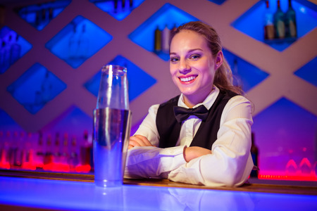 cocktail shaker: Portrait of confident young barmaid sitting by cocktail shaker at counter Stock Photo