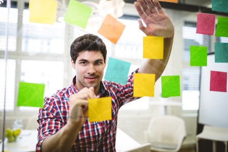 sticky notes: Businessman writing on multi colored sticky notes in creative office