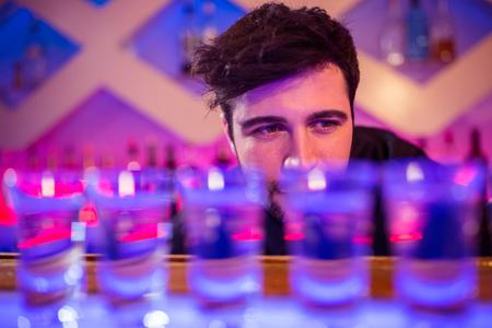 shot glasses: Bartender looking at shot glasses on illuminated bar counter Stock Photo