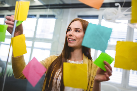 sticky notes: Attractive businesswoman attaching sticky notes on glass in creative office Stock Photo