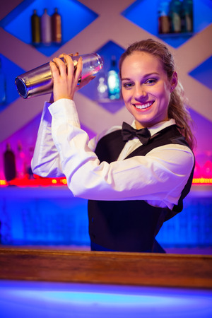 cocktail shaker: Portrait of young barmaid with cocktail shaker at illuminated counter Stock Photo