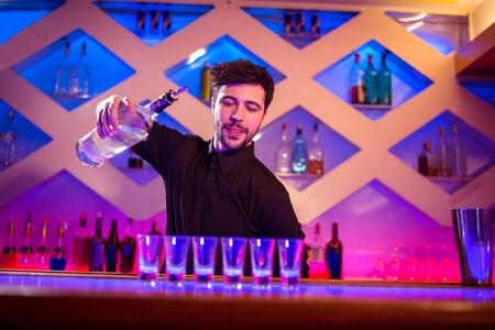 shot glasses: Bartender pouring alcohol in shot glasses on illuminated bar counter