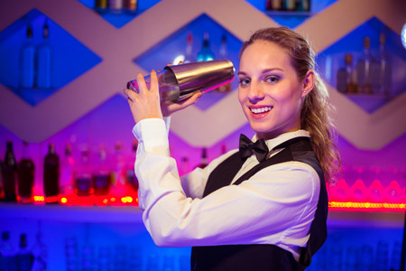cocktail shaker: Portrait of beautiful barmaid with cocktail shaker at illuminated counter Stock Photo