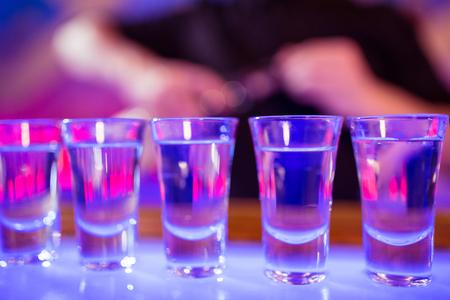 shot glasses: Close-up of shot glasses arranged on illuminated bar counter Stock Photo