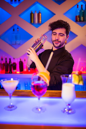 cocktail shaker: Handsome bartender with cocktail shaker at illuminated bar counter Stock Photo