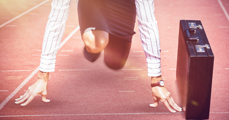 Businesswoman in starting position against focus of athletics track