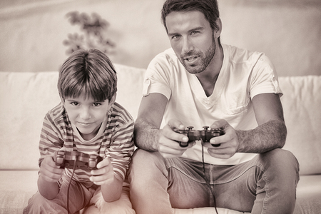 playing video games: Father and son playing video games on the couch