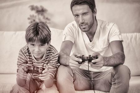jugando videojuegos: Padre e hijo jugando videojuegos en el sof�