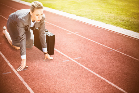 starting position: Businesswoman in starting position against focus on track on a sunny day Stock Photo