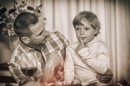 Father with his son sitting on lap at home in the living room photo
