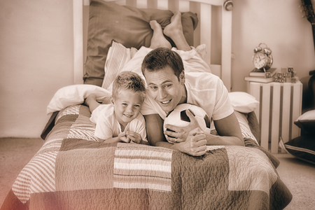 Smiling little boy and his father watching a football match in the kids bedroom photo