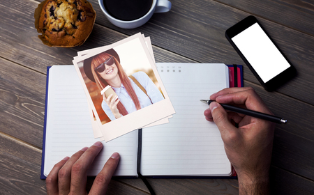 person writing: Smiling hipster woman drinking coffee against person writing on a diary at the desk