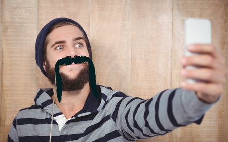 making face: Hipster making face while taking selfie on mobile phone against artificial mustache