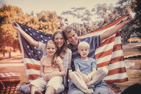 banderas america: familia feliz que sostiene el indicador americano en el parque en un día soleado