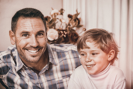 Portrait of smiling father and his son at home in the living room photo