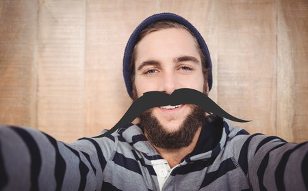 hooded shirt: Portrait of happy hipster with hooded shirt against artificial mustache Stock Photo