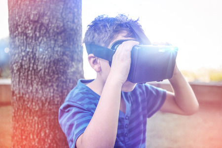 looking through an object: Elementary boy looking through virtual reality headset in school library