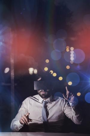 overworking: Businessman using virtual reality device at night