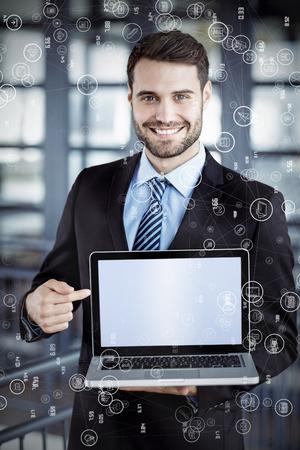 stubble: Sphere of icons against happy businessman showing laptop