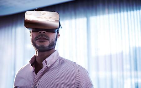 composite image: Composite image of landscape against businessman using an oculus Stock Photo