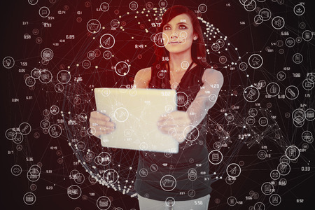 dark haired: Elegant dark haired model holding tablet looking up against glowing sphere on black background Stock Photo