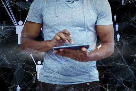mid section: Mid section of man using tablet against futuristic black background with figures Stock Photo