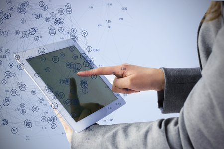using tablet: Businesswoman using a tablet pc against sphere of icons Stock Photo