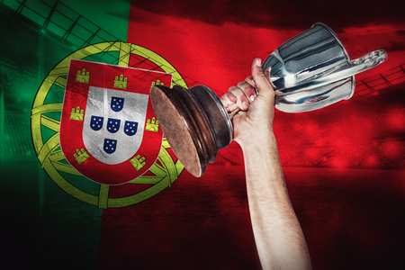 portugese: Happy rugby player holding trophy against digitally generated portugese national flag Stock Photo
