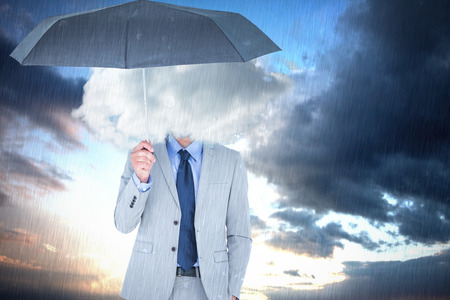 smother: Smiling businessman looking at camera under umbrella against cloudy sky