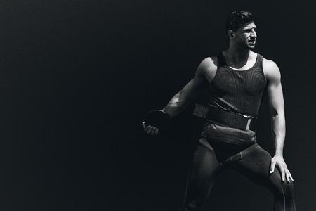 discus: Portrait of sportsman practising discus throw  against black background