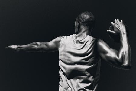 lanzamiento de disco: Vista trasera del deportista practicando el lanzamiento de disco contra el fondo negro