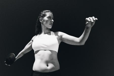 lanzamiento de disco: Vista frontal de la deportista practicando el lanzamiento de disco contra el fondo negro