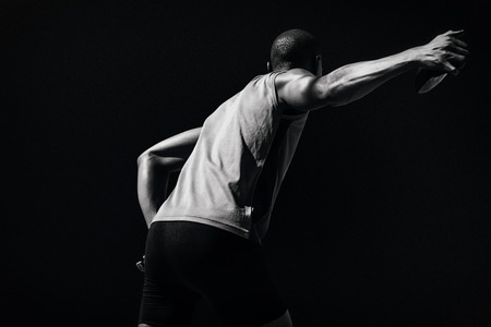 discus: Rear view of sportsman practising discus throw against black background